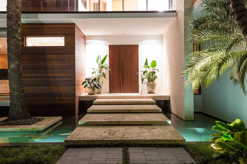 Upon arriving at this modern house, there's a small bridge to cross above thereflecting ponds, before reaching the wood front door. #Bridge #Landscaping #WaterFeature #WoodFrontDoor