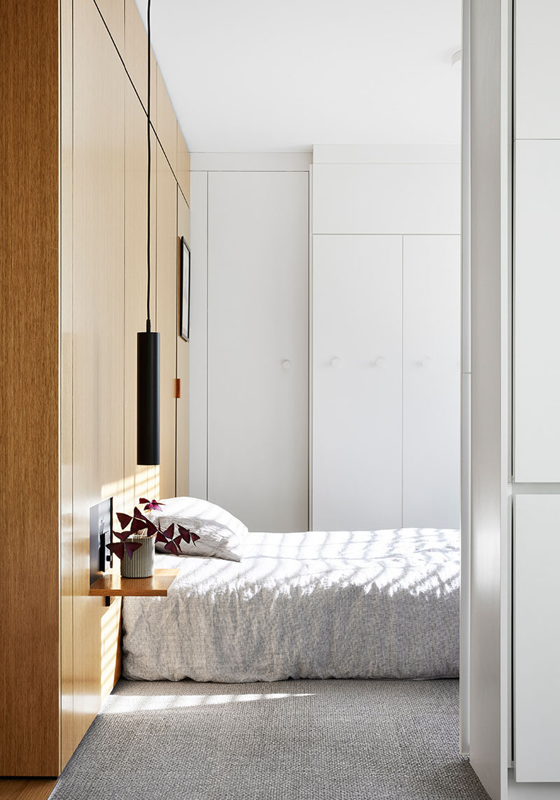 This modern and minimalist bedroom features wood accent wall that becomes the headboard, with a small cut-out revealing a small wall panel that folds down to form the bedside table. #ModernBedroom #WoodAccentWall