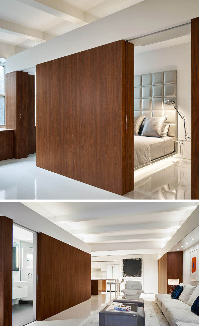 Hidden within the wood walls of this modern apartment, are pocket doors that can be opened to reveal the bedroom and bathroom. #PocketDoors #WoodWalls