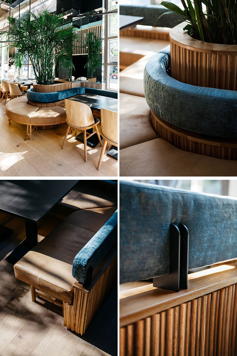This modern restaurant features curved banquette seating that wraps around planters with tall plants, that are reflected in the mirror on the wall. #Banquette #RestaurantDesign ModernRestaurant