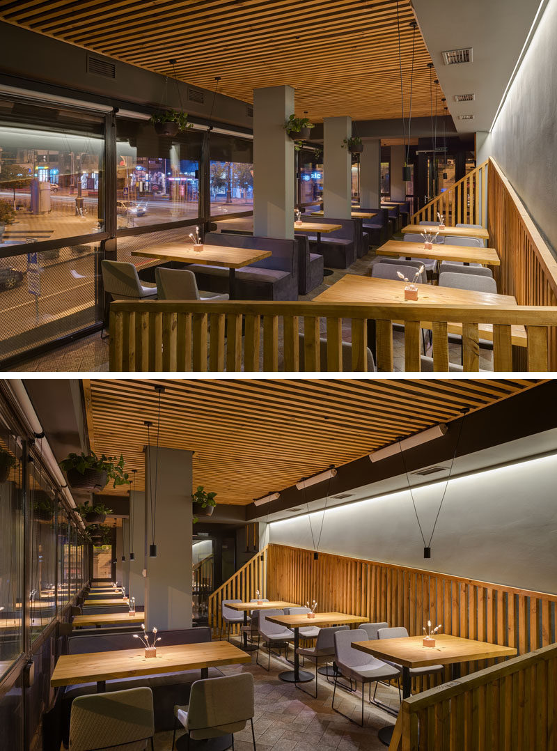 In this modern restaurant, large windows provide a street view for the diners, while behind them, an angled wood slat detail breaks up the grey wall. #RestaurantDesign #InteriorDesign