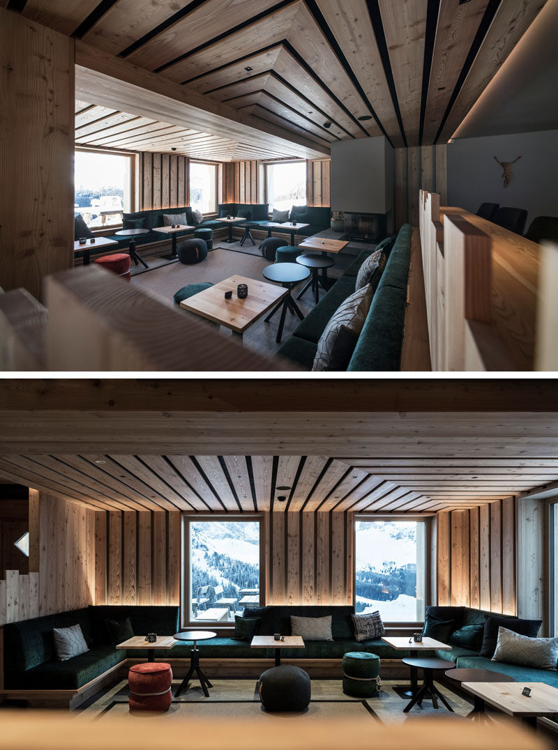 This modern hotel lounge has large windows that frame the view outside, custom built-in seating the wraps around the space, and a fireplace. #HotelDesign #Seating #Fireplace #HotelLounge