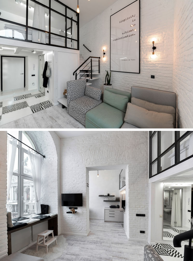 This modern loft apartment features high ceilings, painted brick walls, and a mezzanine with a bedroom and reading room. #LoftApartment #MezzanineBedroom #InteriorDesign #ModernApartment