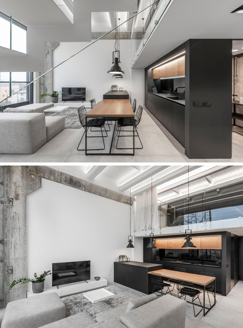 Separating the living room and kitchen in this modern loft apartment, is an island that drops down to become a wood dining table for four. #DiningTable #BlackKitchen #InteriorDesign