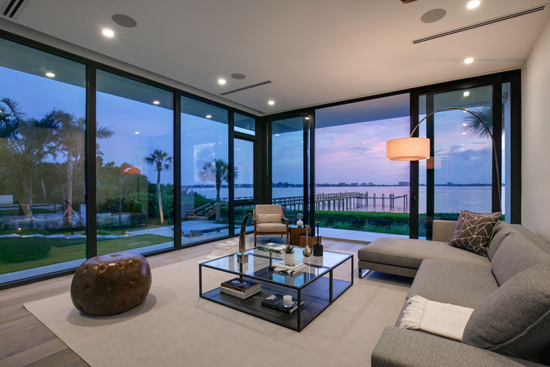 This living room has floor to ceiling windows that provide views of the backyard and water. #Windows #LivingRoom