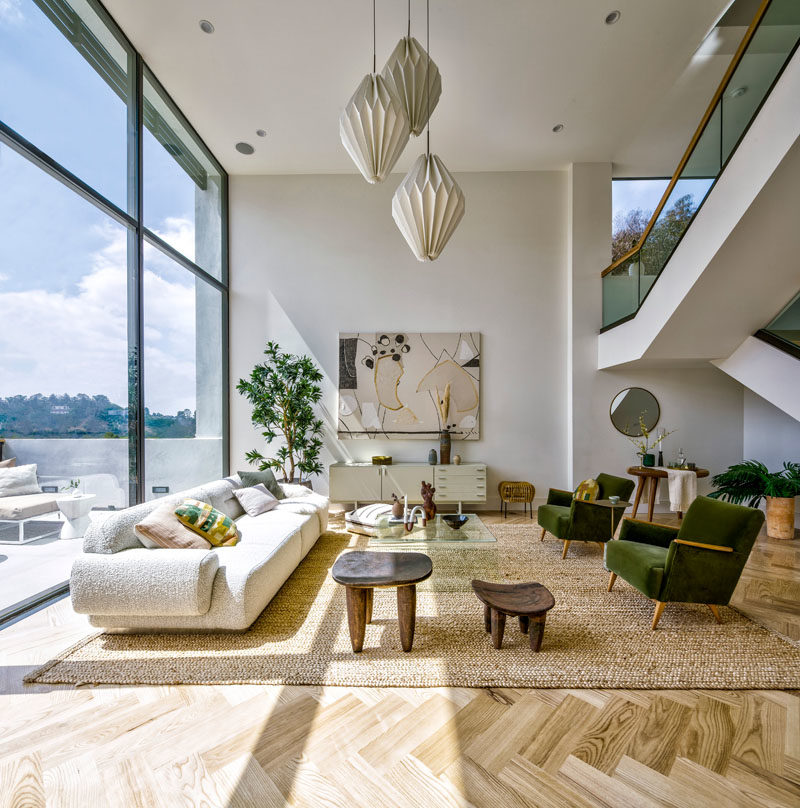 Living Room Ideas - This modern living room has floor-to-ceiling windows that provide a view of the neighborhood. #HighCeilings #LivingRoomIdeas #WindowIdeas