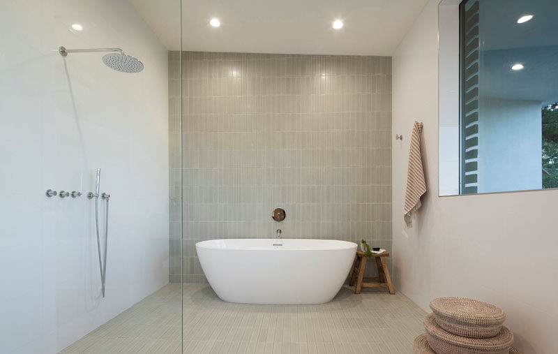 Bathroom Ideas - In this modern bathroom, a wall of vertical tiles acts as a backdrop for the freestanding bathtub. #BathroomIdeas #ModernBathroom