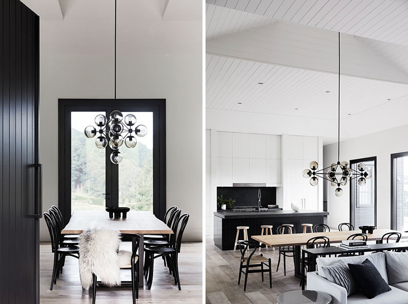 Dining Room Ideas - Stepping inside this modern farmhouse, the double-height ceilings in the open plan interior contribute to the sense of spaciousness, while floor-to-ceiling glass doors and windows offer a strong connection to the outdoors, and frame views of the surrounding farmland. #DiningRoom #DiningRoomIdeas #ModernFarmhouse