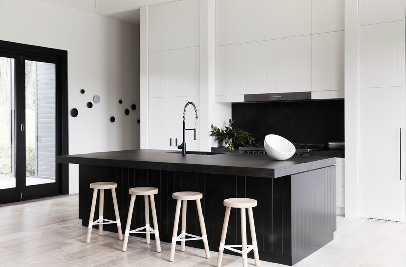 Kitchen Ideas - In this modern farmhouse kitchen, there's a new 9 foot (3m) central island with a black stone countertop and wood paneling, that also strongly contrasts the crisp white cabinets on the wall behind it. #KitchenIdeas #FarmhouseKitchen #BlackAndWhite #KitchenDesign