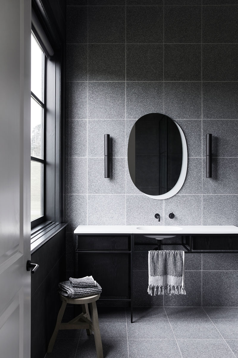 Bathroom Ideas - In this modern grey, black and white bathroom, grey tiles are combined with a black-framed vanity and a white countertop that has a built-in basin. #BathroomIdeas #BathroomDesign #ModernBathroom