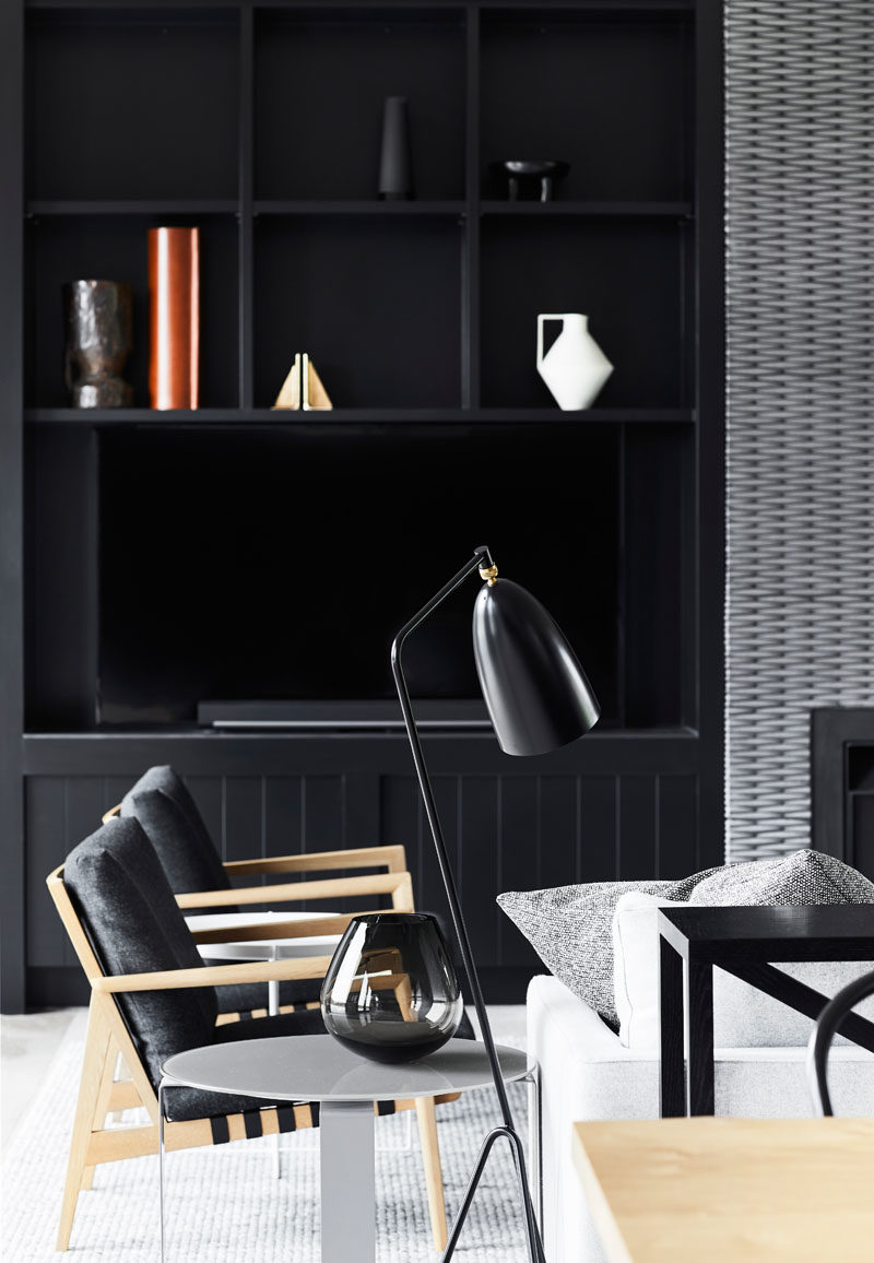 Shelving Ideas - Custom-designed shelving has been added on either side of the fireplace, providing dedicated areas for displaying decorative elements. #BlackShelving #Fireplace #ModernLivingRoom