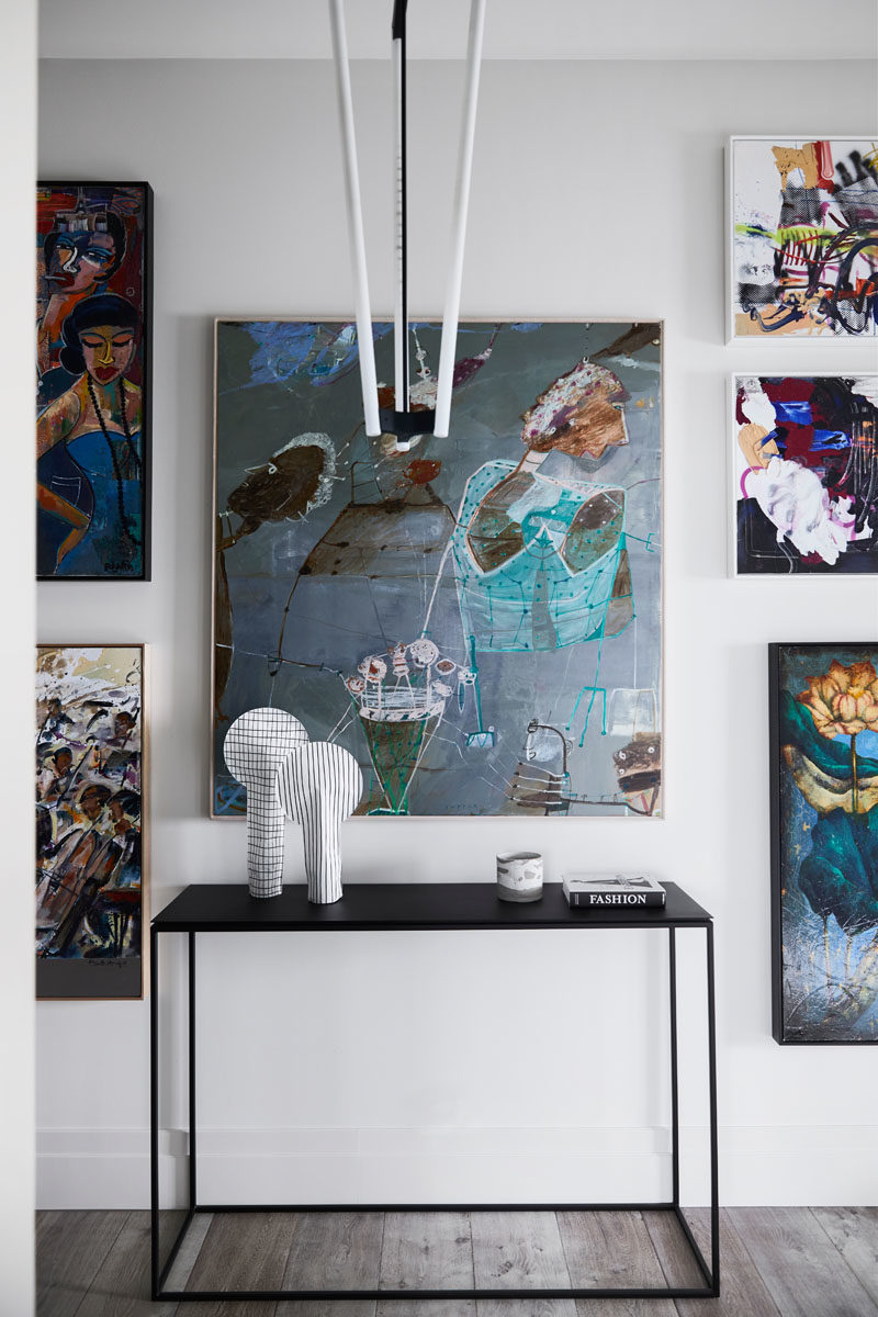 Decor Ideas - Modern and colorful artwork has been positioned around a minimalist black console table. #ModernDecor #ModernArt #DecorIdeas