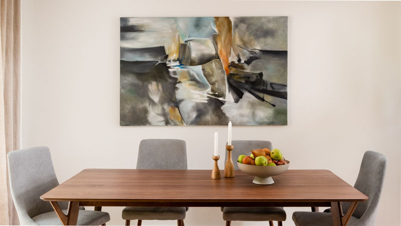 Dining Room Ideas - This modern dining room features a modern wood table and light grey chairs, that are complemented by a bespoke art piece on the wall. #DiningRoomIdeas #ModernDiningRoom #DiningRoomDesign