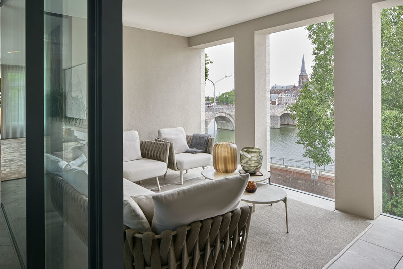 Outdoor Spaces - This modern penthouse apartment has a covered outdoor patio that overlooks the nearby river. #OutdoorSpace #CoveredPatio #OutdoorLounge