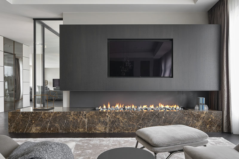 Fireplace Ideas - This modern sitting area is focused on the recessed television and the open linear fireplace below. #FireplaceIdeas #LinearFireplace #RecessedTV