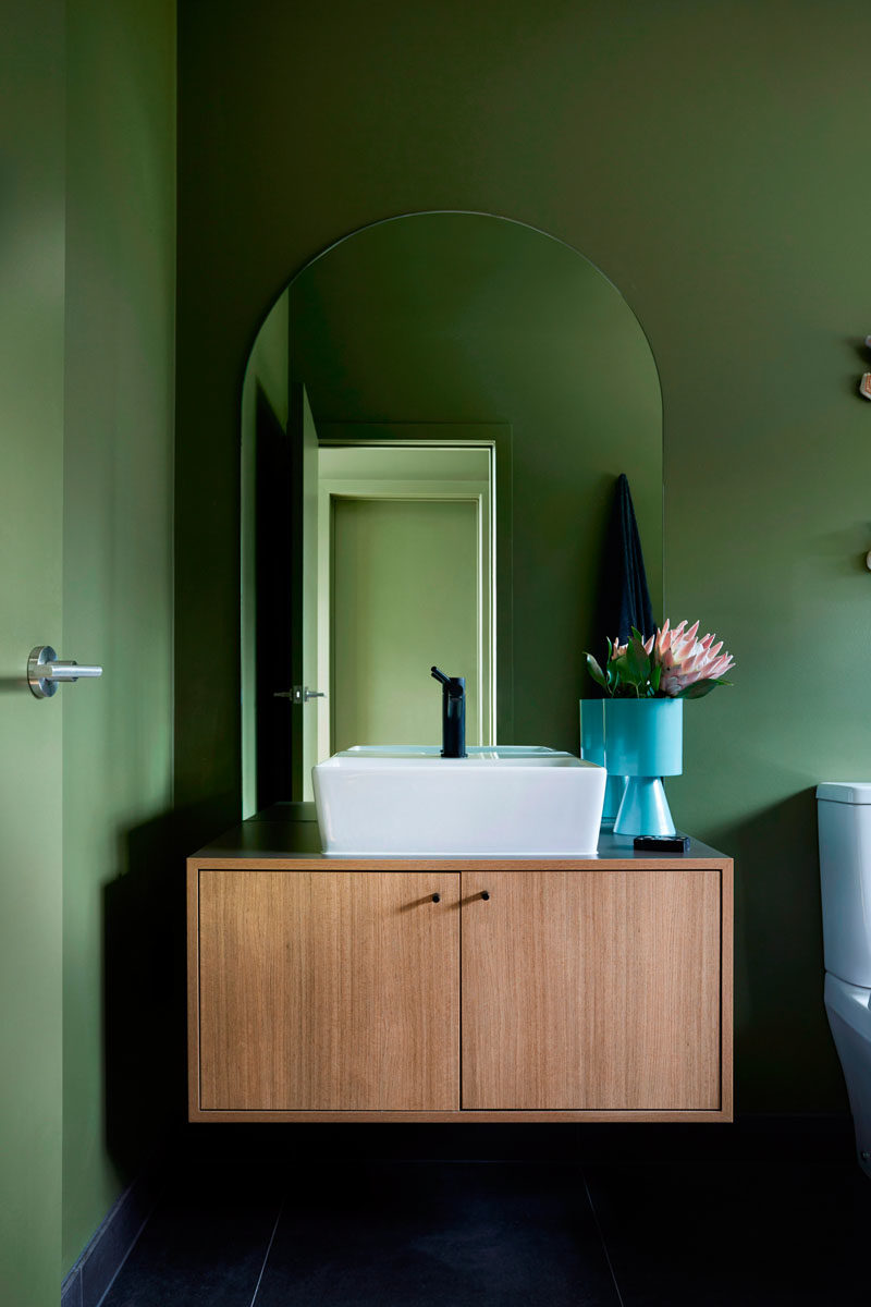 In this modern bathroom, a floating wood vanity sits below an arched mirror, while a vase adds a pop of bright blue. #BathroomDesign #ModernBathroom