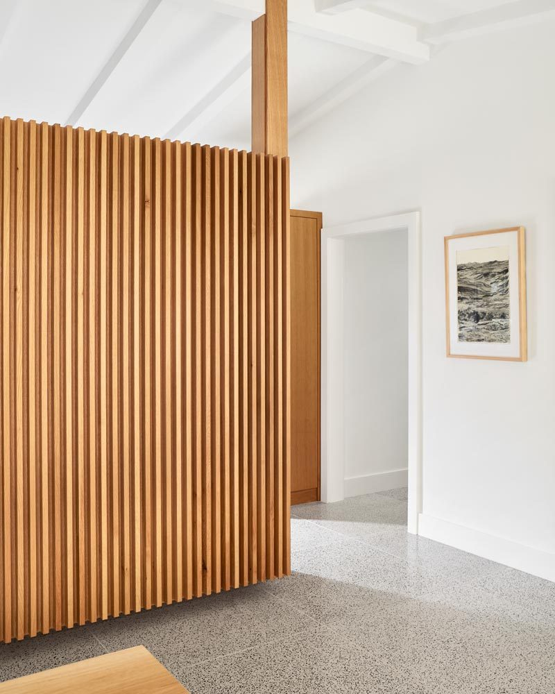 This renovated mid-century ranch house includes new custom details, like this wood paneling, while terrazzo floors have been installed throughout. #WoodPaneling #MidCenturyModern #TerrazzoFloors