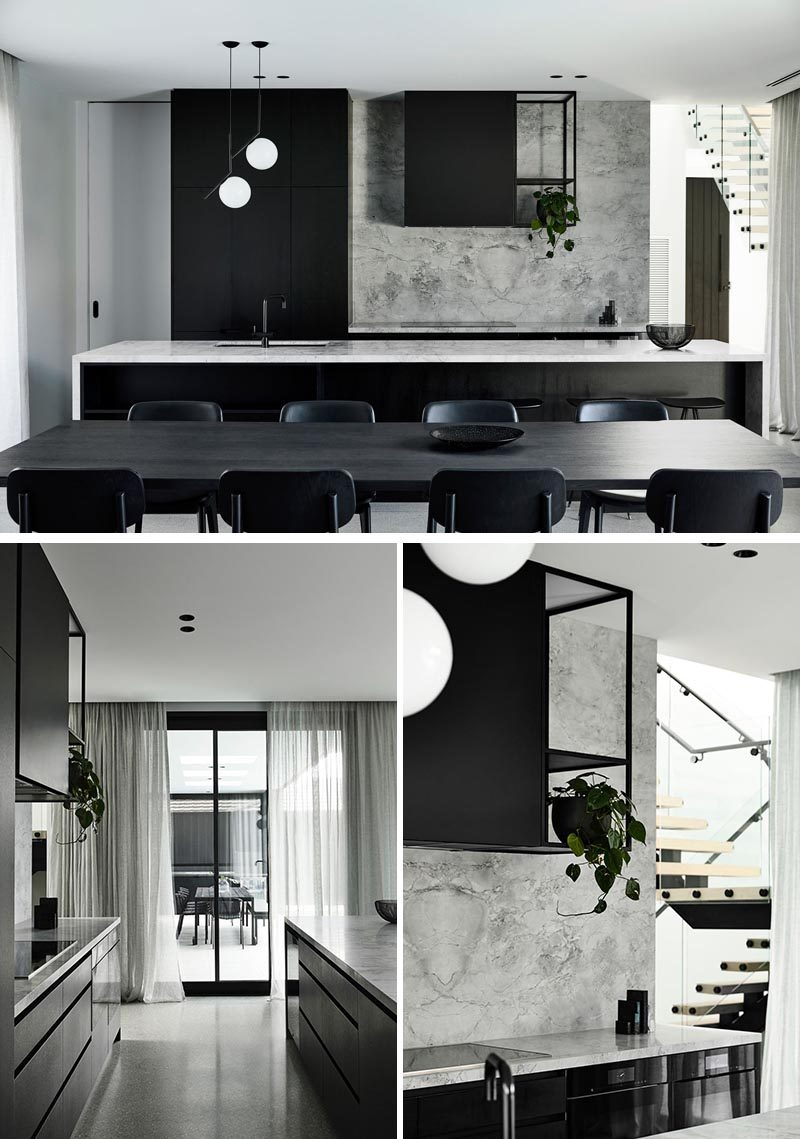 White veined marble lines the kitchen walls and countertops, providing tonal contrast to the black joinery. #ModernKitchen #BlackAndGreyKitchen #KitchenDesign