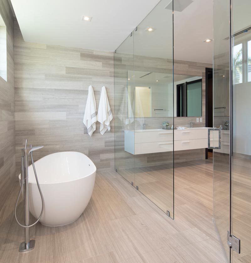 This modern master bathroom features a floating double-sink vanity, wood-like tile floors and walls, frosted doors, and a glass enclosed wet room that houses the shower and bath. #ModernBathroom #WetRoom #BathroomDesign #InteriorDesign #MasterBathroom