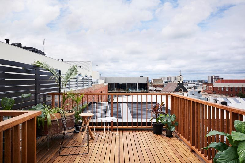 This wooden rooftop deck sits high above the neighborhood, creating an outdoor space where the rooftop views can be enjoyed. #RooftopDeck #Architecture