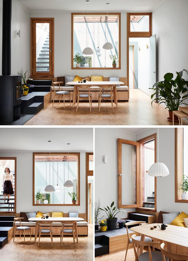 This casual and modern dining area has built-in bench seating and a large window. Stairs lead from the dining area up to a rooftop deck. #DiningRoom #BuiltInBench #Windows #Stairs