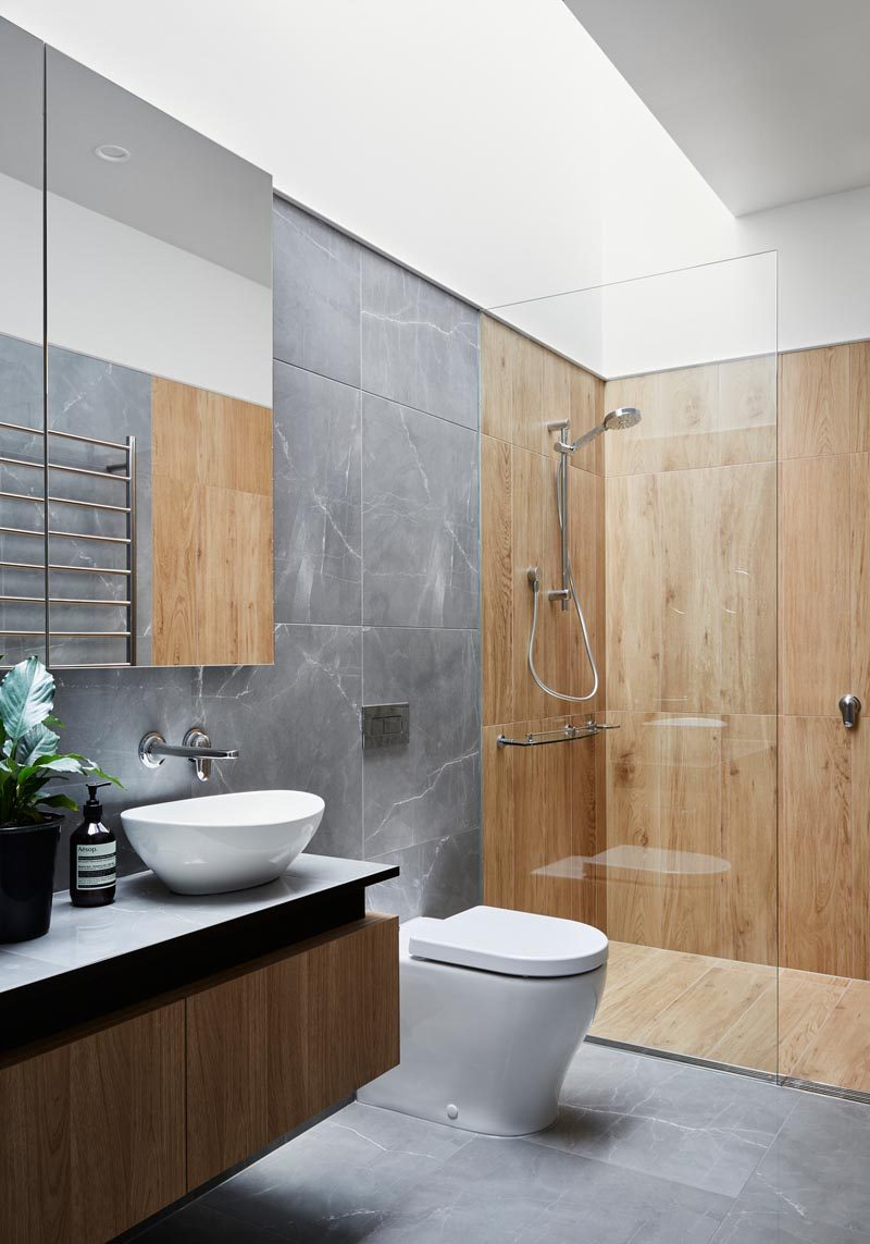 In this modern bathroom, a skylight brightens the space and highlights the wood-like tiles in the shower, and the grey tiles in the rest of the space. #BathroomDesign #ModernBathroom