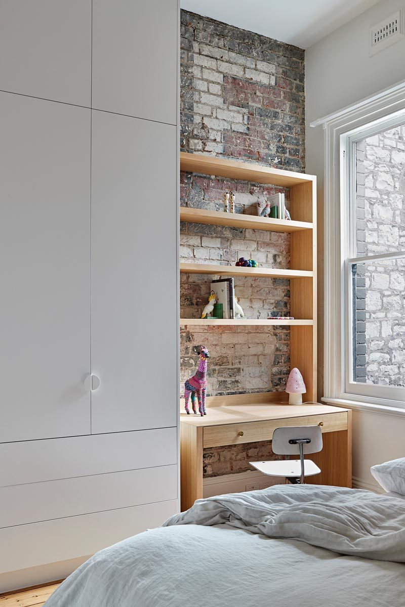 In this modern kid's bedroom, the original brick wall becomes the backdrop for a homework station. #ModernKidsBedroom #HomeworkStation