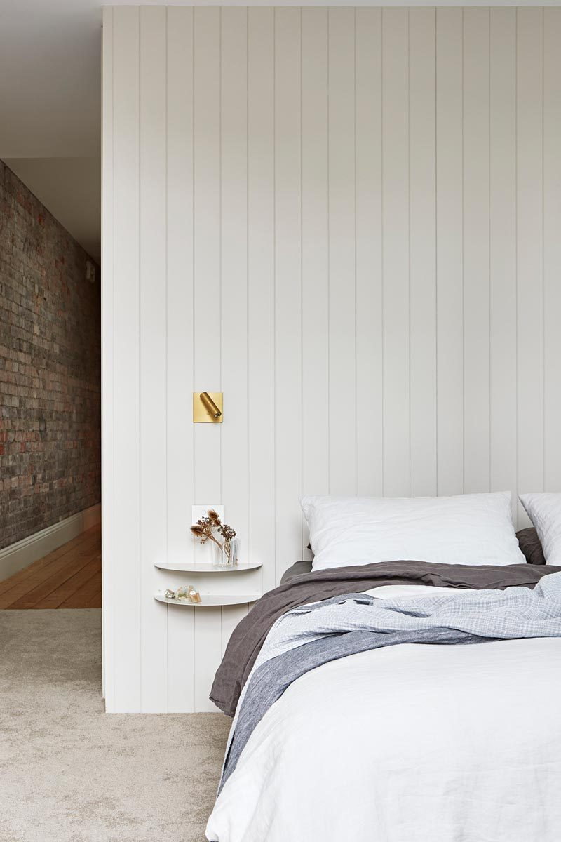 In this modern master bedroom, two simple curved floating shelves are attached to the wall and act as a bedside table. #ModernBedroom #BedroomDesign #MasterBedroom