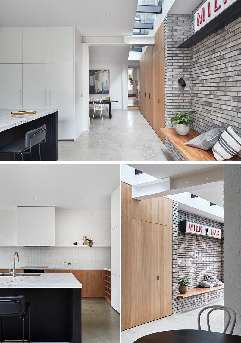 In this modern house extension, Polished concrete flooring complements the grey brick accent, while the  built-in wood bench sits opposite the kitchen. White and wood cabinets, a  black island, and light Carrara stone countertops have been combined to  create a modern and open kitchen. #ModernInterior #ConcreteFloors #ModernKitchen