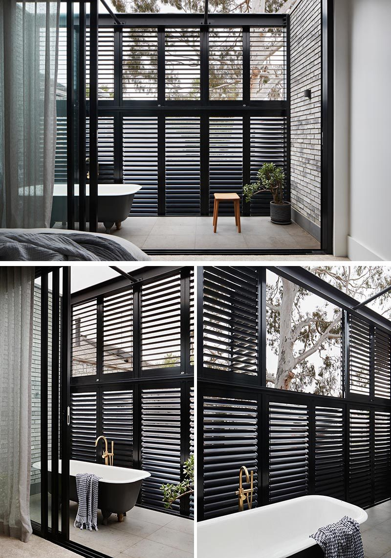 This modern bedroom enjoys a private balcony with a bath, so that the home owner could live out the dream of soaking in a steamy hot bath under the canopy of the stars and the gum tree. The black slat screen allows the breeze to filter through and also acts as a privacy screen. #ModernBedroom #ModernBalcony #OutdoorBathtub