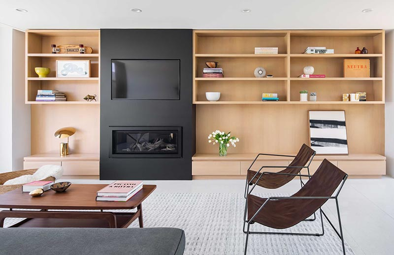 The linear fireplace with a matte black frame is located below a TV that's been recessed into the black accent wall, creating a unified accent in living room that contrasts the light wood. #BuiltInTV #BuiltInTelevision #RecessedTelevision #LinearFireplace #LivingRoomIdeas #Shelving #ModernLivingRoom