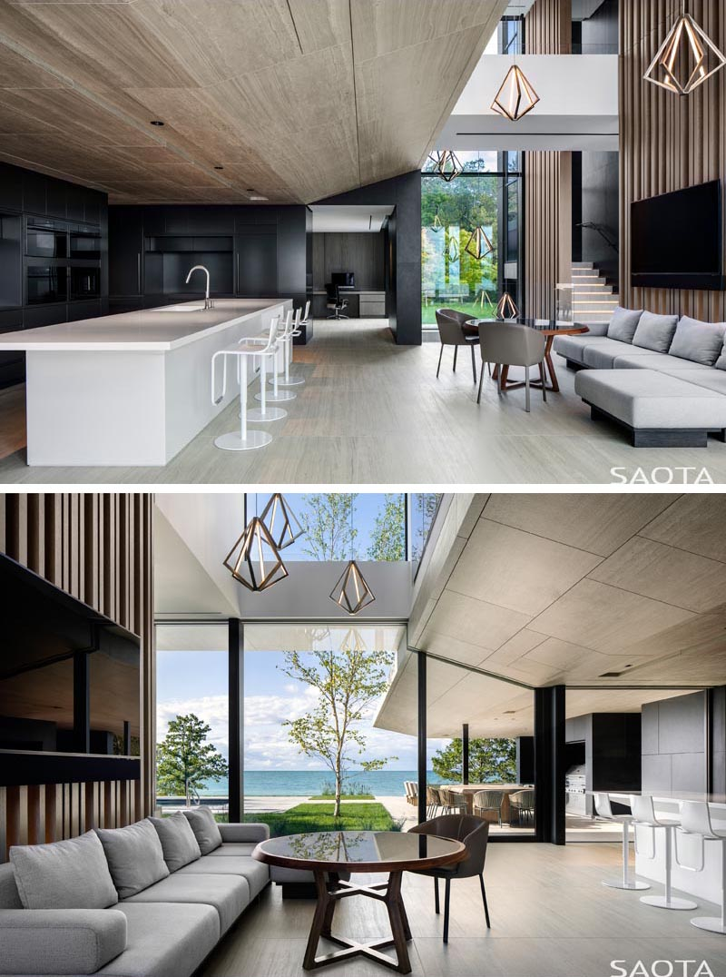 A tall partition separates the dining area from a secondary seating area that faces the modern black kitchen with a large white island. #ModernKitchen #BlackAndWhiteKitchen #MinimalistKitchen