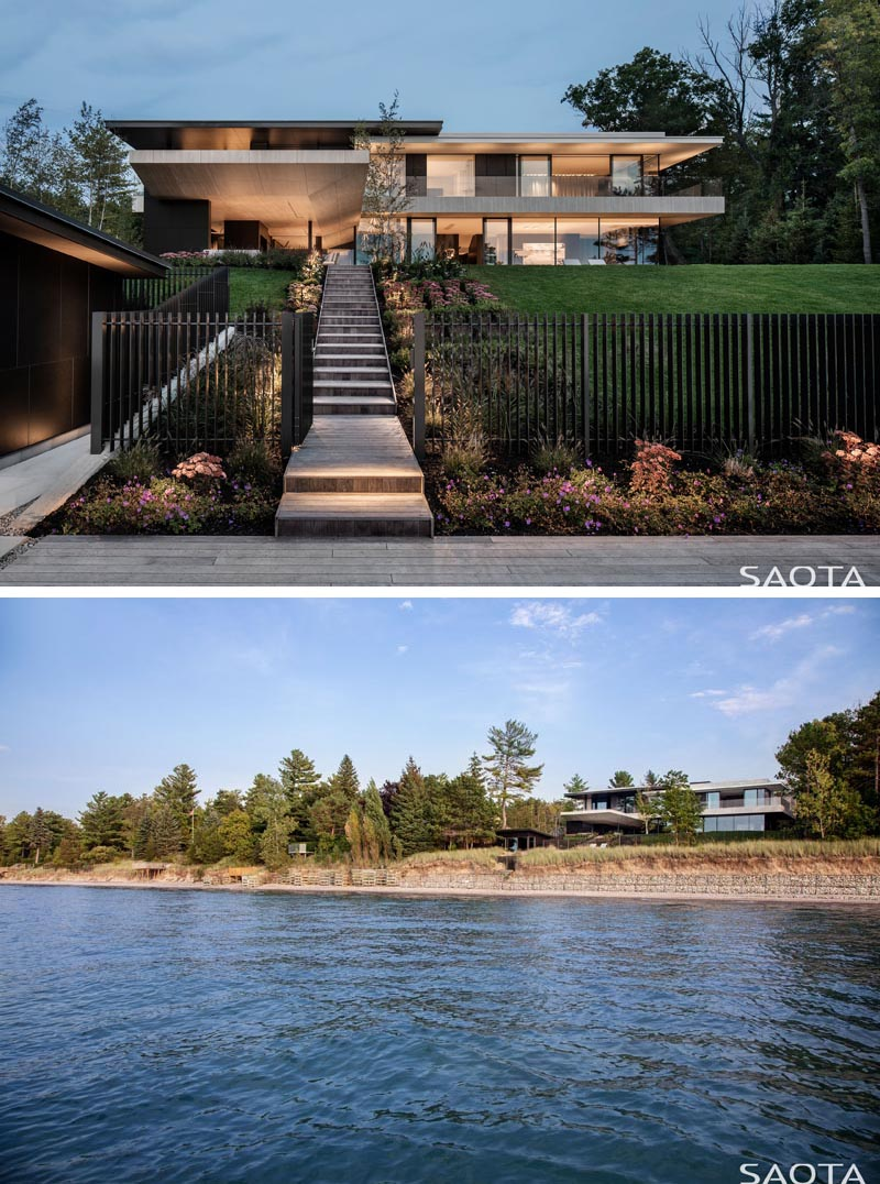 This modern lake house has stairs that travel down the slope to a refurbished cabin that predates the house, and is now a guest suite or an additional outdoor entertaining area. #ModernLakeHouse #ExteriorStairs #Landscaping