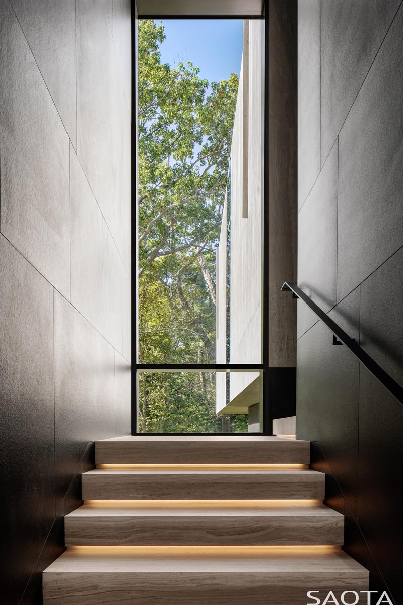 This modern staircase is lined with the same ceramic panels as the exterior of the house, while the wood stair treads have hidden lighting underneath them, and a tall window provides views of the trees. #StairDesign #TallWindow #StairsWithLighting