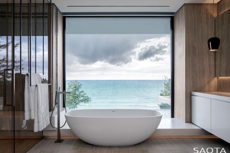 In this modern master bathroom, a freestanding bathtub is located directly in front of a large picture window that provides an uninterrupted view of the lake, and looks like a moving painting. #ModernMasterBathroom #BathroomDesign #FreestandingBathtub #PictureWindow