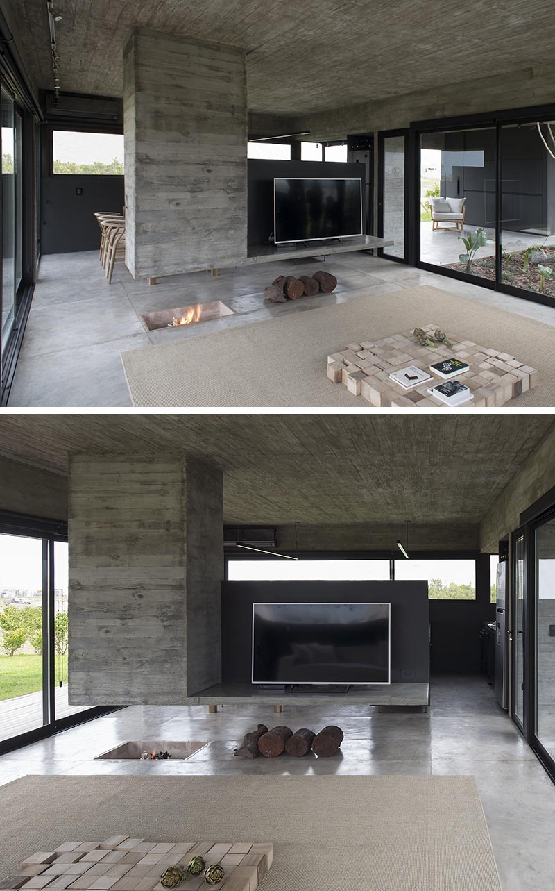Designed as a sculptural element that separates the dining room and the living room, this modern hanging concrete divider has a chimney built into it on one end, and the other is a platform for holding the television. Underneath, the fireplace has been built into the ground. #Fireplace #RoomDivider #ConcreteDivider #HangingConcreteChimney #TVStand #Concrete