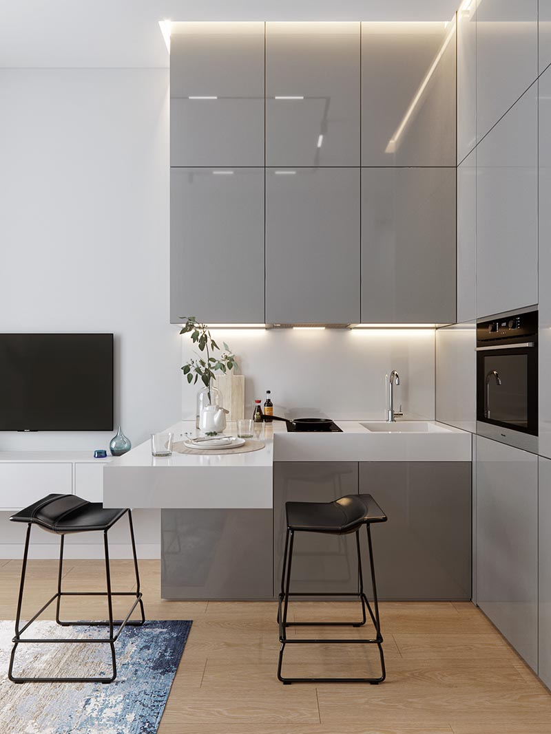A small kitchen with an L-shaped countertop, integrated fridge, minimalist grey cabinets, hidden lighting, and a cantilevered peninsula for dining. #SmallKitchen #TinyKitchen #KitchenDesign #KitchenLayout