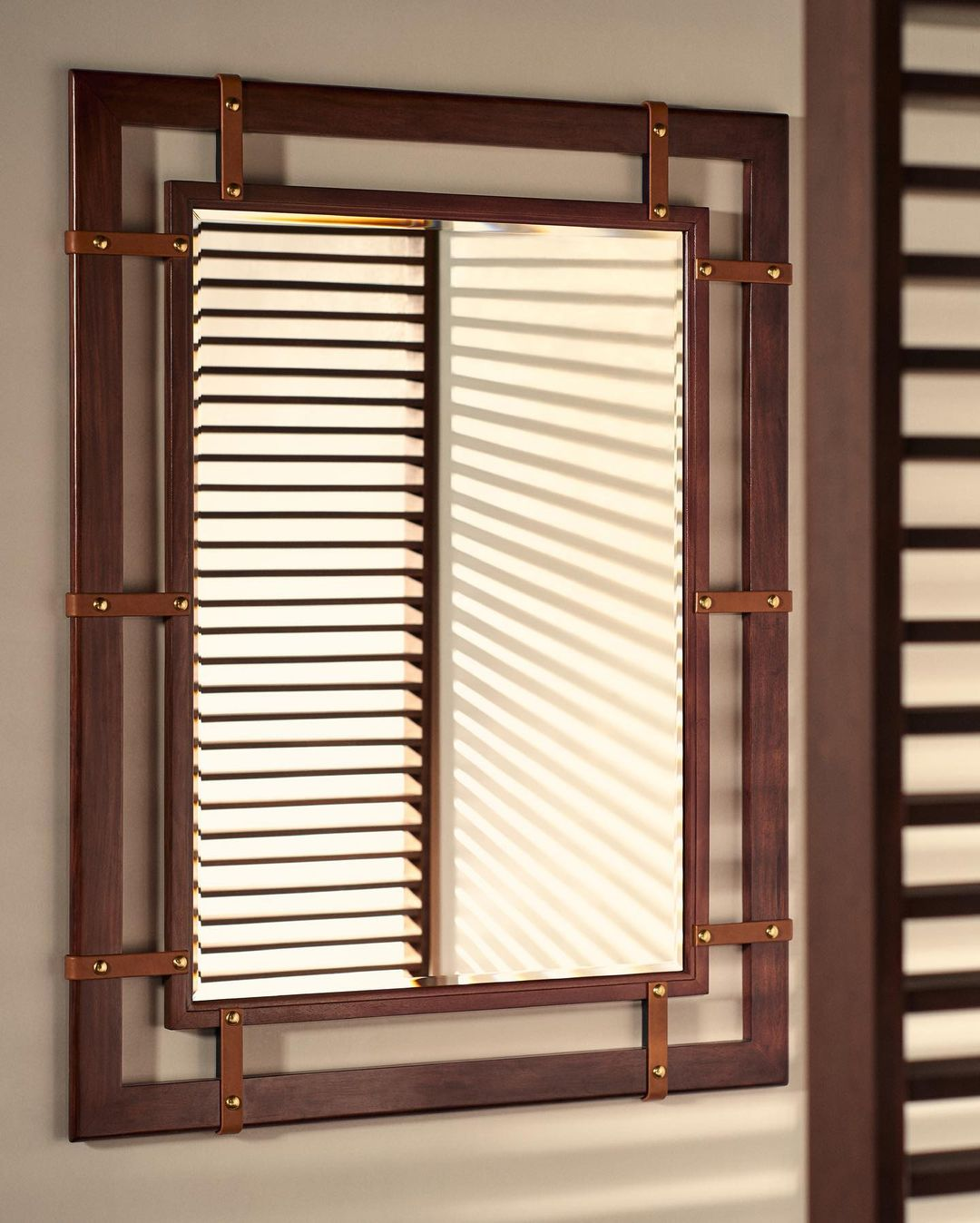 The chestnut-framed Nolan mirror features leather straps and brass nailheads for...