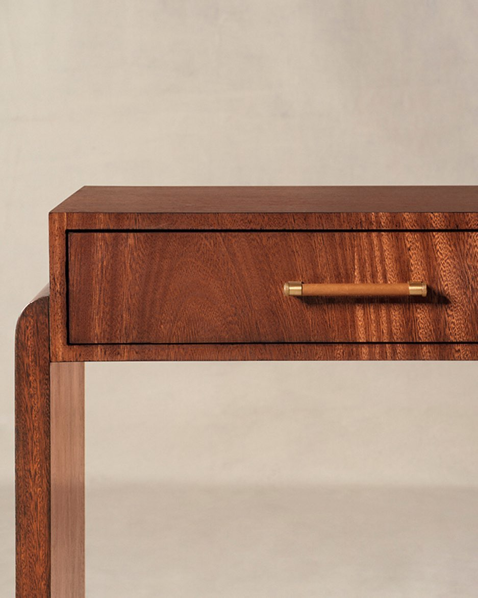 The sleek Thayer Console in blonde mahogany features chic leather-wrapped brass ...