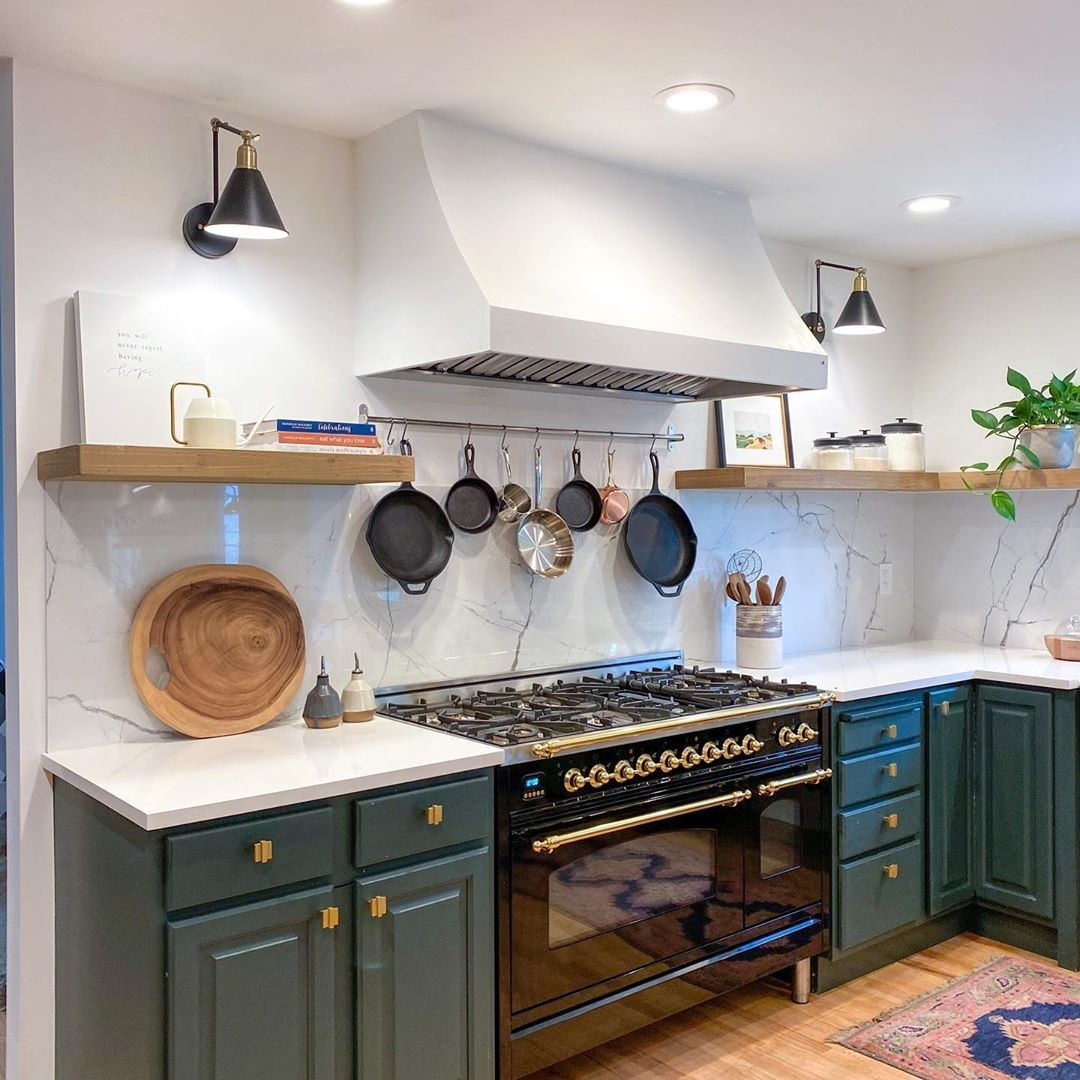 Emerald green cabinetry combines with go...